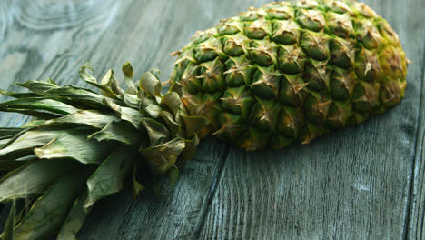 Half-of-pineapple-on-wooden-table