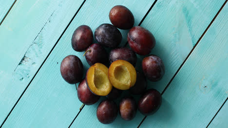 Pile-of-ripe-plums-on-blue-wood