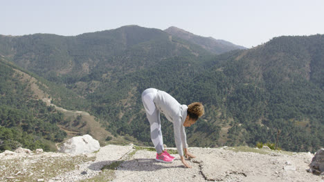 Yougn-female-stretching-on-rock