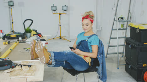 Woman-resting-with-smartphone-at-carpenter-workbench-