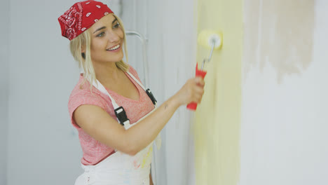Smiling-female-painting-wall-with-roller-