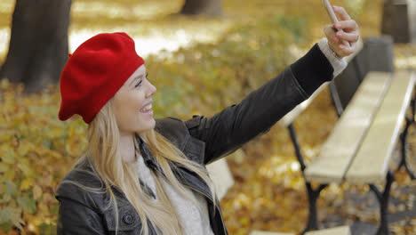 Woman-in-beret-taking-selfie-in-park