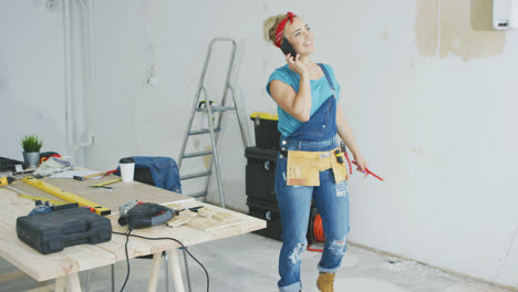 Cheerful-female-carpenter-talking-on-smartphone-