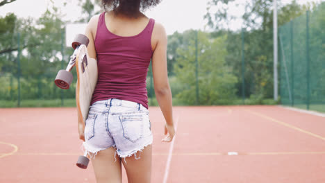 Girl-with-skateboard-on-sports-ground