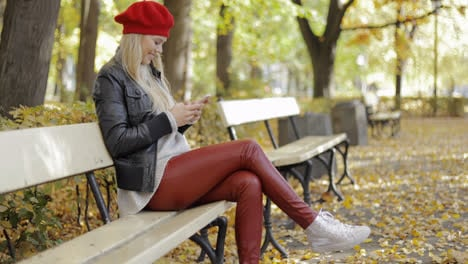 Smiling-woman-in-beret-using-smartphone