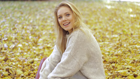 Cheerful-woman-sitting-on-ground
