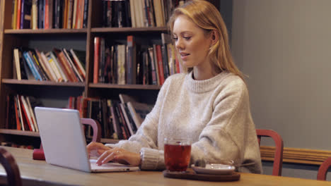 Attractive-woman-in-jumper-using-laptop