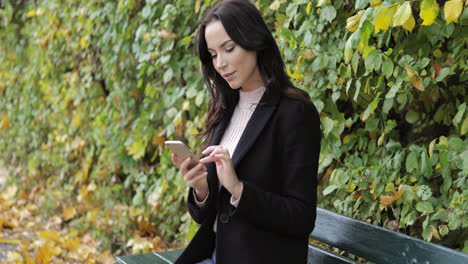 Woman-using-smartphone-on-bench