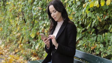 Mujer-Con-Smartphone-En-Banco