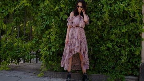 Stylish-hipster-girl-posing-over-green-leaves-bush-background