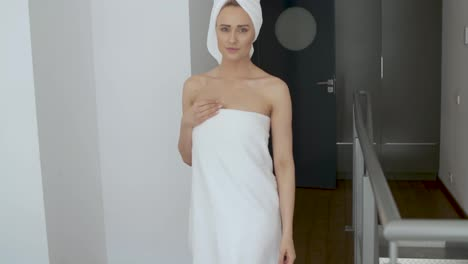 Beautiful-middle-aged-blonde-woman-wrapped-in-towel-white-towel-walking