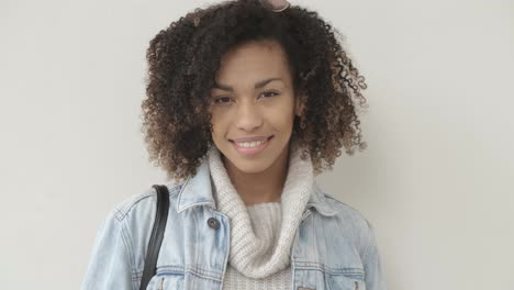 Afro-American-girl-in-casual-clothes-is-looking-at-camera-and-smiling