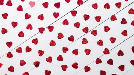 Vlentine-s-Day-composition-Heart-shaped-sequins-placed-on-white-wooden-table