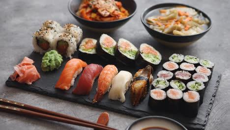 Varios-Tipos-De-Sushi-Colocados-En-Tablero-De-Piedra-Negra