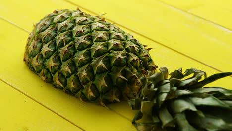Half-of-pineapple-on-yellow-wood