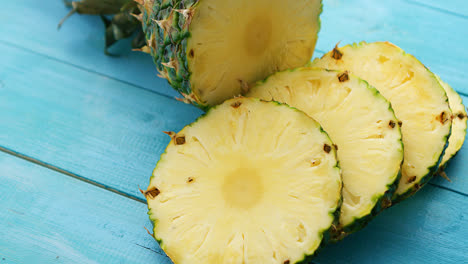 Slices-of-pineapple-on-blue-wood