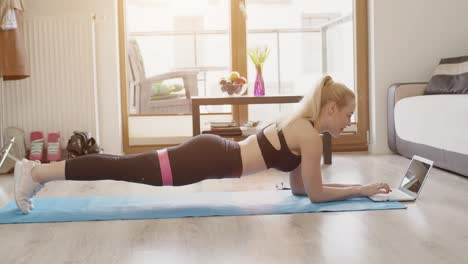 Beautiful-blond-sporty-woman-doing-her-workout-at-home-while-watching-online-lessons