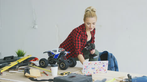 Female-with-radio-controlled-car-using-laptop