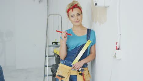 Smiling-woman-carpenter-leaning-on-wall-