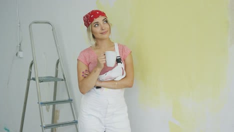 Smiling-woman-painter-standing-with-drink