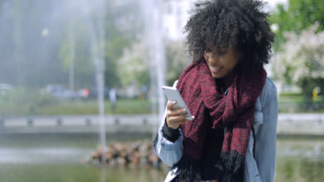Smiling-girl-with-phone-on-fountain
