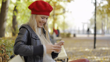 Woman-in-beret-using-smartphone-in-park