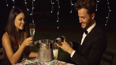 Man-fills-his-glass-with-champagne-to-toast