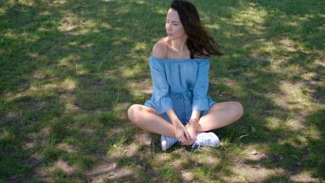 Portrait-of-attractive-brunette-woman-in-blue-dress-sitting-in-a-park