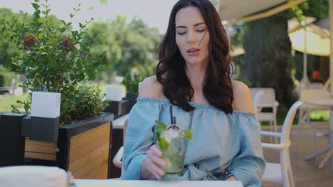 Beauiful-woman-sitting-in-outdoor-restaurant-and-sip-mojito-dring-in-summer-hot-day