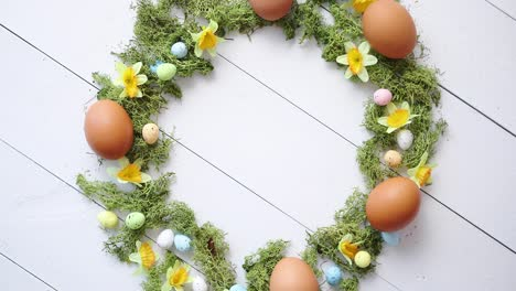Colorful-decorative-Easter-eggs-wreath-on-white-wooden-table-background