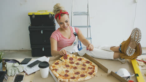 Woman-in-overalls-eating-pizza-at-workplace-
