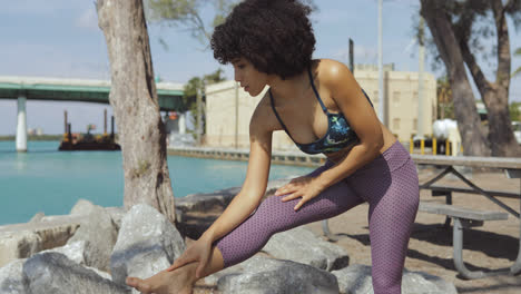 Black-woman-stretching-on-riverbank