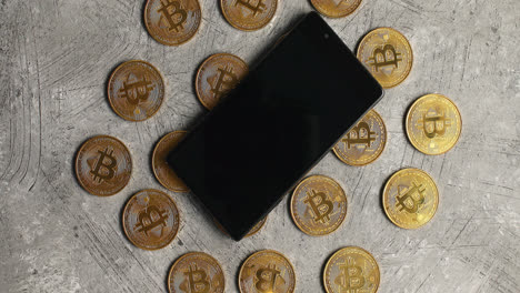 Smartphone-and-bticoin-on-gray-background