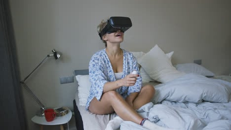 Amazed-woman-in-VR-headset-on-bed