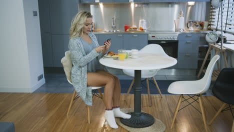 Attractive-woman-using-smartphone-during-breakfast