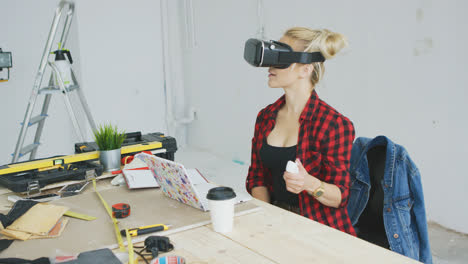 Female-in-virtual-reality-headset-at-laptop-