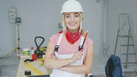 Female-construction-worker-standing-at-workbench-