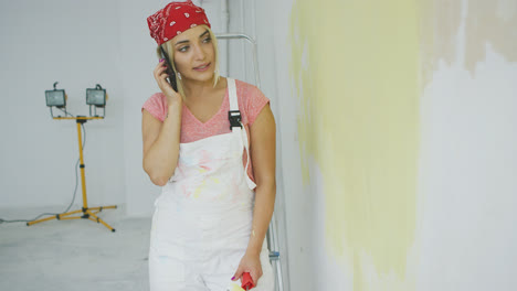 Woman-talking-on-smartphone-at-half-painted-wall