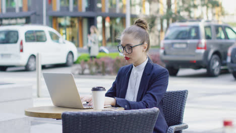 Businesswoman-with-laptop-in-outside-cafe
