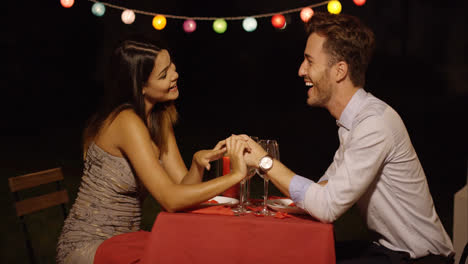 Couple-holds-hands-across-table-and-smiles