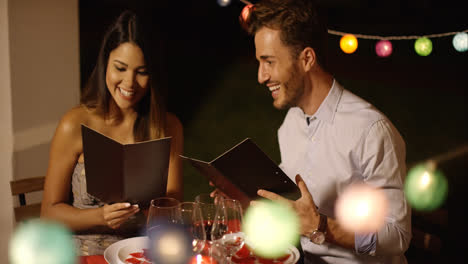 Young-couple-laughing-as-they-go-through-the-menu