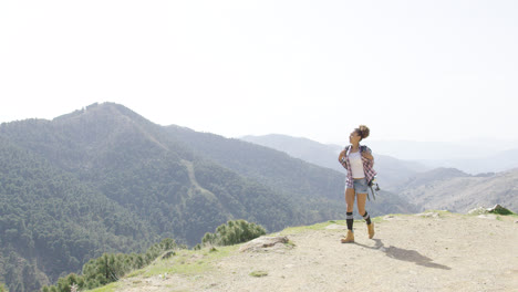 Female-backpacker-walking-on-top-of-mountain