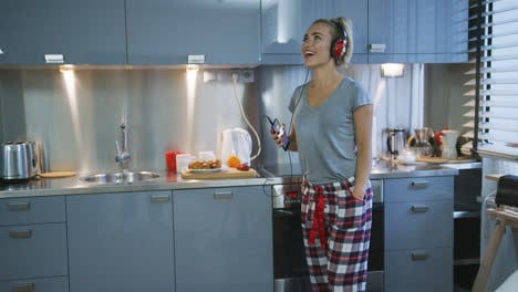 Woman-listening-to-music-in-kitchen