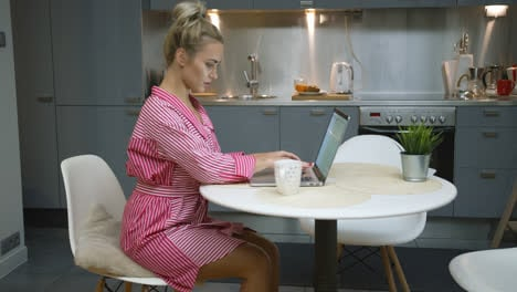 Woman-using-laptop-in-kitchen
