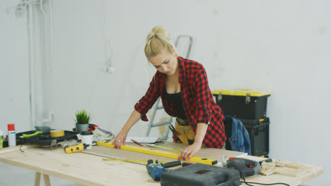 Woman-using-spirit-level-on-workshop-desk-