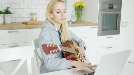 Girl-practicing-guitar-and-using-laptop-
