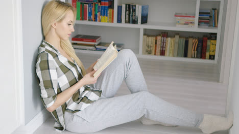 Woman-sitting-on-floor-with-book