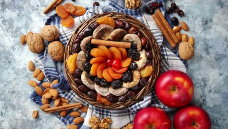 Composition-of-dried-fruits-and-nuts-in-small-wicker-bowl-placed-on-stone-table