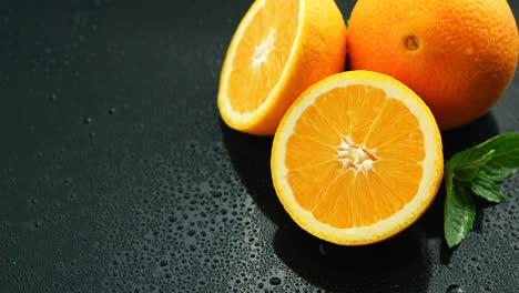Naranja-Con-Hoja-Sobre-Mesa-Mojada