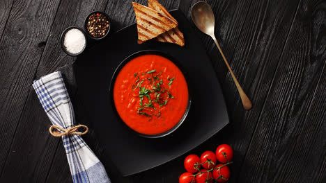 Tomato-soup-in-black-bowl-with-crisp-bread-